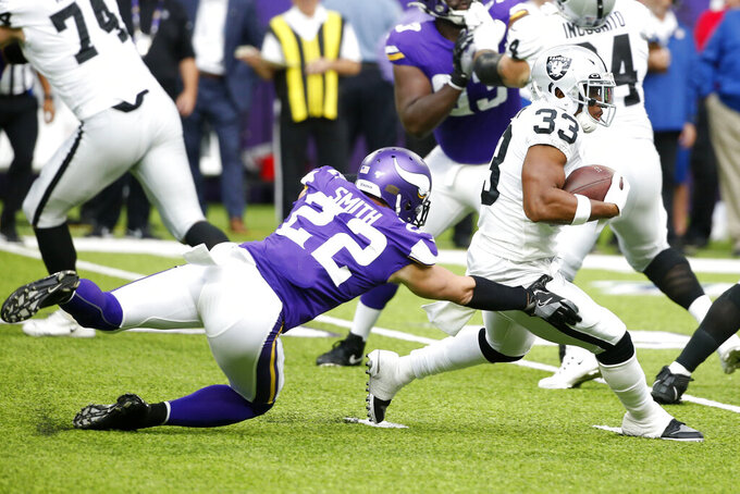 Oakland Raiders running back DeAndre Washington (33) is tackled by Minnesota Vikings free safety Harrison Smith (22) during the first half of an NFL football game, Sunday, Sept. 22, 2019, in Minneapolis. (AP Photo/Bruce Kluckhohn)