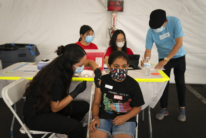 FILE - In this Aug. 28, 2021, file photo, Mayra Navarrete, 13, receives the Pfizer COVID-19 vaccine from registered nurse, Noleen Nobleza at a clinic set up in the parking lot of CalOptima in Orange, Calif. With more than 40 million doses of coronavirus vaccines available, U.S. health authorities said they're confident both seniors and other vulnerable Americans seeking booster shots and parents anticipating approval of initial shots for young children will have easy access. (AP Photo/Jae C. Hong, File)