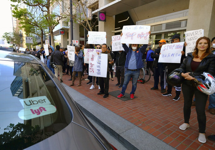 FILE - In this May 8, 2019, file photo, Uber and Lyft drivers carry signs during a demonstration outside of Uber headquarters in San Francisco. The ride-hailing companies Uber and Lyft say they are willing to change the way they treat drivers in California. That could include paying a base wage and providing certain benefits. But the companies are arguing they need to continue to classify drivers as independent contractors, not employees. California lawmakers are considering legislation that would tighten the rules around how companies classify workers as contractors. (AP Photo/Eric Risberg, File)