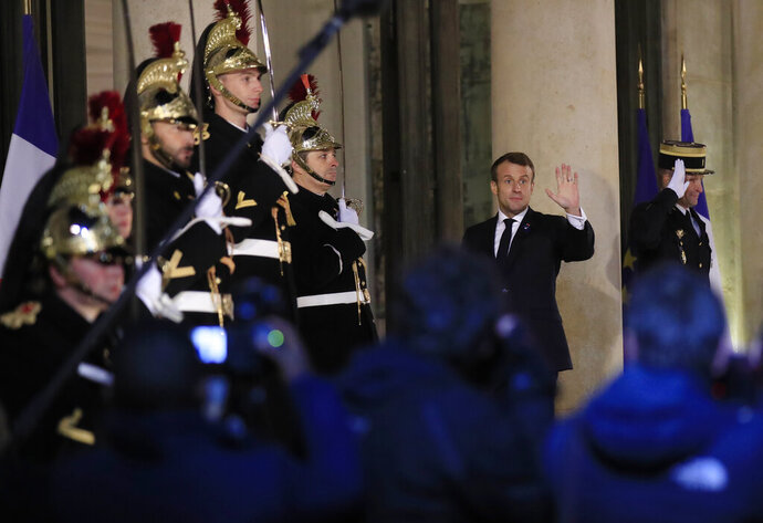 French President Emmanuel Macron waves to the media as he walks in to the the Elysee Palace in Paris, Monday, Nov. 11, 2019, to host. Head of States and officials gathering in Paris for the Peace Forum which starts tomorrow Nov. 12, 2019. (AP Photo/Michel Euler)