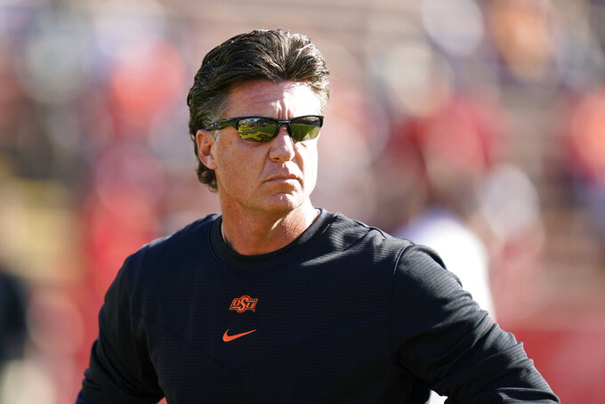 Oklahoma State head coach Mike Gundy stands on the field before an NCAA college football game against Iowa State, Saturday, Oct. 23, 2021, in Ames, Iowa. (AP Photo/Charlie Neibergall)