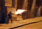 A demonstrator fires fireworks at the police during a protest against President Evo Morales' reelection, in La Paz, Boliva, Tuesday, Nov. 5, 2019. Opponents challenged an official count that showed Morales winning with 47% of the vote and a margin of just over 10 percentage points over his nearest competitor, enough to avoid the need for a runoff against a united opposition. (AP Photo/Juan Karita)