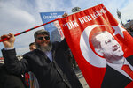 A man gestures before the arrival of Turkey's President Recep Tayyip Erdogan to addresses the supporters of his ruling Justice and Development Party, AKP, at a rally in Istanbul, Tuesday, March 19, 2019, ahead of local elections scheduled for March 31, 2019. (AP Photo/Emrah Gurel)