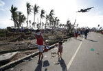 FILE- In this Nov. 11, 2013, file photo, survivors look as a military C-130 plane arrives at typhoon-ravaged Tacloban city, Leyte province central Philippines. Filipinos are facing the powerful Typhoon Mangkhut with the memory of another devastating storm still fresh in their minds. Nearly five years ago, Typhoon Haiyan left more than 7,300 people dead or missing, flattened entire villages, swept ships inland and displaced more than 5 million in the central Philippines, well to the south of Mangkhut's path. (AP Photo/Aaron Favila, File)