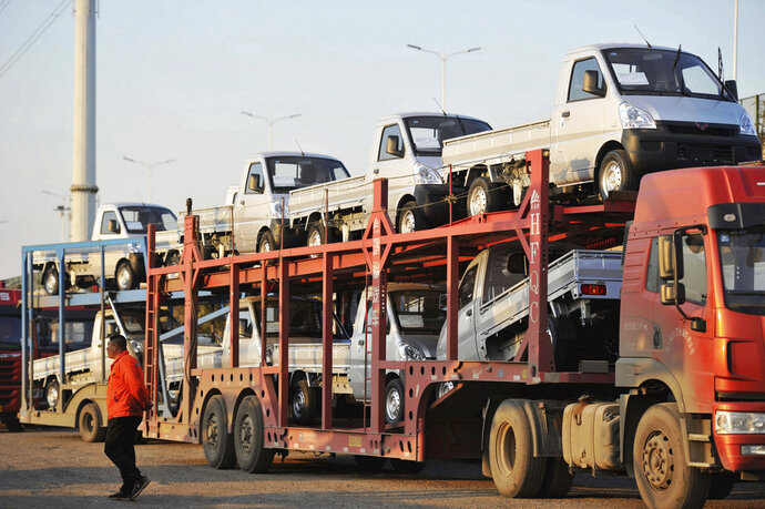 In this Oct. 31, 2018, photo, a staff members walks past a semi truck loaded with new vehicles in the parking lot for a local automaker in Qingdao in eastern China's Shandong province. China's auto sales sank for a fourth month in October, tumbling 13 percent from a year earlier and adding to an unexpectedly painful downturn for global automakers in their biggest market. (Chinatopix via AP)
