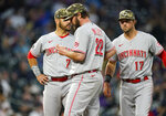 Cincinnati Reds starting pitcher Wade Miley, front, waits to be pulled from the mound as third baseman Eugenio Suarez, back left, and shortstop Kyle Farmer look on in the fourth inning of a baseball game against the Colorado Rockies, Friday, May 14, 2021, in Denver. (AP Photo/David Zalubowski)