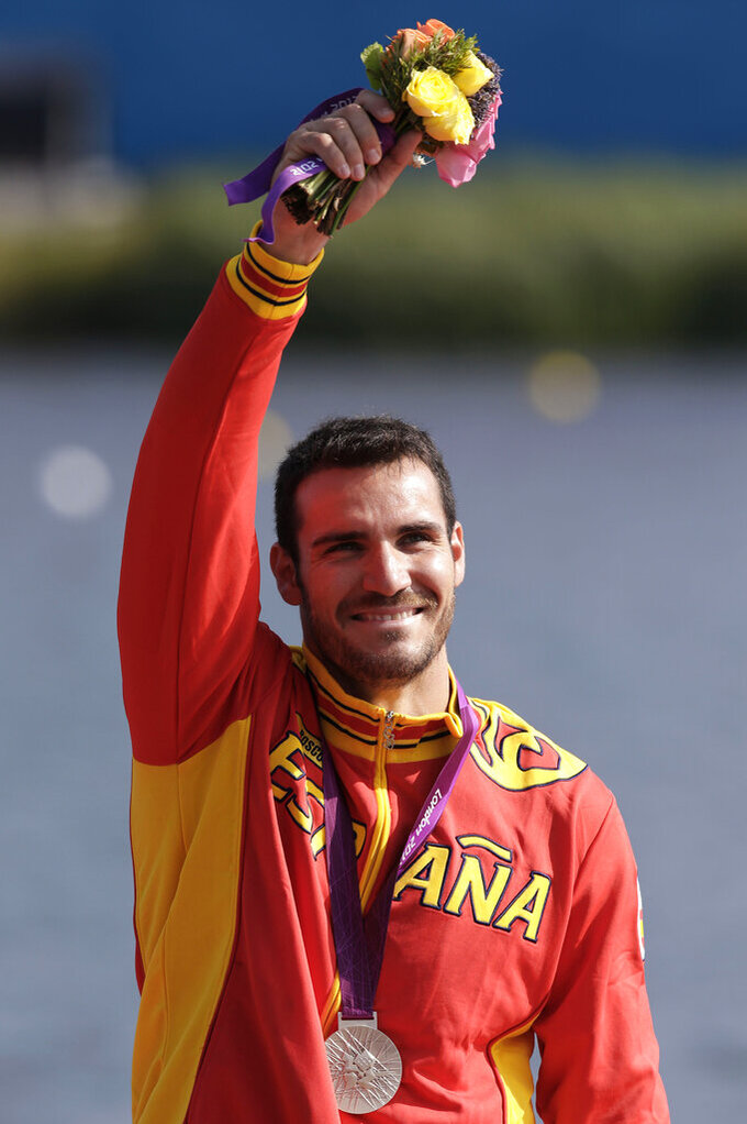 FILE - In this Saturday, Aug. 11, 2012, file photo, Spain's Saul Craviotto Rivero celebrates after winning the silver medal in the men's kayak single 200m in Eton Dorney, near Windsor, England, at the 2012 Summer Olympics. It wasn't long ago that Saul Craviotto was sitting in his kayak contemplating a much-anticipated announcement from the Spanish Olympic Committee but now he is among some of the Spanish athletes and sportspeople who have rejoined the police force to help the hard-hit southern European country during the pandemic. He was set to be named the country's flagbearer for the opening ceremonies in Tokyo. (AP Photo/Natacha Pisarenko)