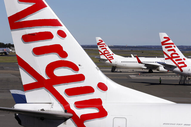 Virgin Australia planes are parked at terminal at Sydney Airport in Sydney, Wednesday, Aug. 5, 2020. Virgin Australia will cut about 3000 jobs as the airline struggles with the effects of the coronavirus pandemic. (AP Photo/Rick Rycroft)