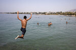 A youth jumps in the sea at a beach of Kavouri suburb, southwest of Athens, on Friday, July 30, 2021. Greek authorities ordered additional fire patrols and infrastructure maintenance inspections Friday as the country grappled with a heat wave expected to last more than a week, with temperatures expected to reach 42 C (107.6 F). (AP Photo/Yorgos Karahalis)