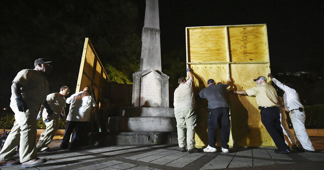 FILE - In an Aug. 15, 2017 file photo, Birmingham city workers use plywood panels to cover the Confederate Monument in Linn Park, in Birmingham, Ala., on orders from Mayor William Bell. Birmingham Mayor Randall Woodfin on Tuesday, Feb. 11, 2020 criticized an Alabama law forbidding the majority-black city from removing, or altering, a Confederate monument as well as new proposal to fine cities $10,000-a-day for violations. Birmingham faces a $25,000 fine for putting wooden panels around a Confederate monument in Linn Park.(Joe Songer/The Birmingham News via AP, File)