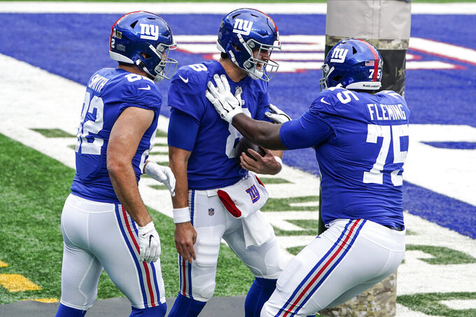 New York Giants quarterback Daniel Jones (8) celebrates with teammates Kaden Smith (82) and Cameron Fleming (75) after rushing for a touchdown during the first half of an NFL football game against the Philadelphia Eagles, Sunday, Nov. 15, 2020, in East Rutherford, N.J. (AP Photo/Seth Wenig)