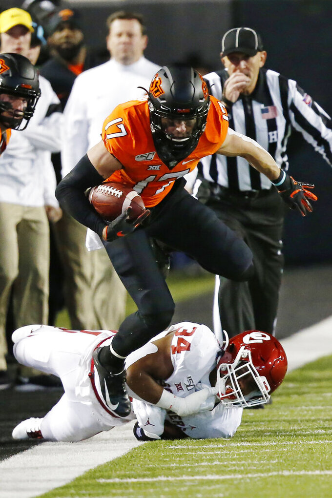 Oklahoma State wide receiver Dillon Stoner (17) jumps over Oklahoma linebacker David Ugwoegbu (34) in the first half of an NCAA college football game in Stillwater, Okla., Saturday, Nov. 30, 2019. (AP Photo/Sue Ogrocki)