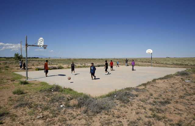 FILE - In this Sept. 25, 2014, file photo, students play basketball at Little Singer Community School in Birdsprings, Ariz., on the Navajo Nation. Basketball is woven in the fabric of Native American life. Now, during a global pandemic, the balls have all but stopped bouncing. Already hit hard by the coronavirus outbreak, Native Americans are faced with life without basketball — or any other sport - for the forseeable future. (AP Photo/John Locher, File)