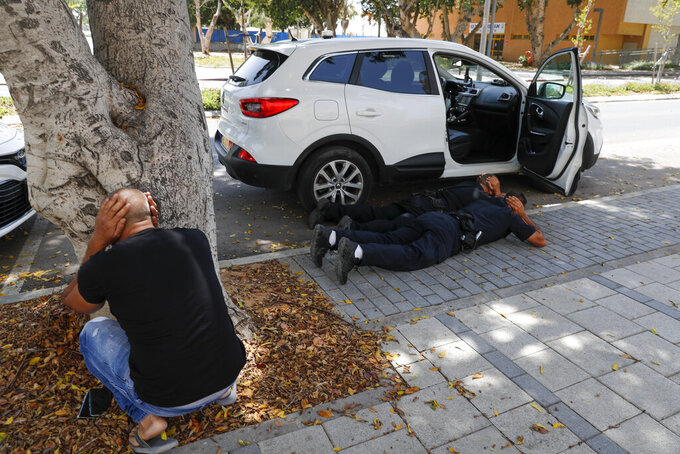 People take cover as a siren sounds a warning of incoming rockets fired from the Gaza strip, in the southern Israeli town of Ashkelon, Tuesday, May 11, 2021. (AP Photo/Ariel Schalit)