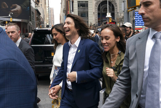 Vladimir Tenev, CEO and co-founder of Robinhood, center, walks in New York's Times Square following his company's IPO, Thursday, July 29, 2021. Robinhood is selling its own stock on Wall Street, the very place the online brokerage has rattled with its stated goal of democratizing finance. Through its app, Robinhood has introduced millions to investing and reshaped the brokerage industry, all while racking up a long list of controversies in less than eight years. (AP Photo/Mark Lennihan)