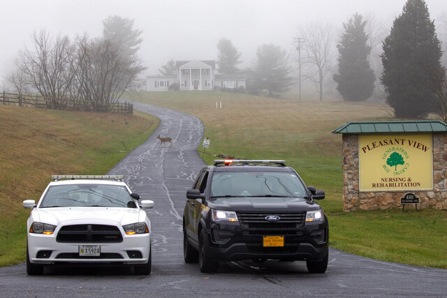 A deer crosses through the fog as a Carroll County Sheriff officer and a Maryland State Trooper guard the driveway to the Pleasant View Nursing Home, in Mount Airy, Md., Sunday, March 29, 2020. Maryland's governor said Saturday night that the nursing home had been struck by an outbreak of COVID-19. (AP Photo/Jacquelyn Martin)