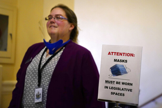 Rep. Amanda Collamore, R-Pittsfield, wears a face shield on her way to the first legislative session in the State House since the proceedings were moved to the more spacious Augusta Civic Center, Wednesday, June 2, 2021, in Augusta, Maine. (AP Photo/Robert F. Bukaty)