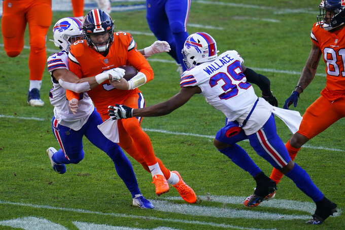 Denver Broncos quarterback Drew Lock, center, is brought down by Buffalo Bills cornerback Levi Wallace (39) and outside linebacker A.J. Klein during the first half of an NFL football game Saturday, Dec. 19, 2020, in Denver. (AP Photo/Jack Dempsey)