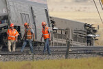 Workers walk Sunday, Sept. 26, 2021, next to cars from an Amtrak train that derailed Saturday just west of Joplin, Mont. The westbound Empire Builder was en route to Seattle from Chicago, with two locomotives and 10 cars. (AP Photo/Ted S. Warren)