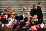 French President Emmanuel Macron, left, and Chinese President Xi Jinping react as schoolchildren wave Chinese and French flags during a welcome ceremony at the Great Hall of the People in Beijing, Wednesday, Nov. 6, 2019. (AP Photo/Mark Schiefelbein)