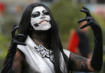 A performer poses for a photo during the Day of the Dead parade in Mexico City, Saturday, Nov. 2, 2019. (AP Photo/Ginnette Riquelme)