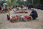 A man lays flowers at a grave of Captain 2nd rank Alexander Avdonin, one of the 14 crew members who died in a fire on a Russian navy's deep-sea research submersible, at the Serafimovskoye memorial cemetery during a funeral ceremony in St. Petersburg, Russia, Saturday, July 6, 2019. Russian President Vladimir Putin has awarded the nation's highest honors to 14 seamen who died in a fire on one of the navy's research submersibles. (AP Photo/Dmitri Lovetsky)