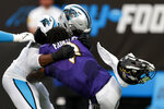 Carolina Panthers defensive end Brian Burns knocks the helmet off Baltimore Ravens quarterback Tyler Huntley during the first half of a preseason NFL football game Saturday, Aug. 21, 2021, in Charlotte, N.C. (AP Photo/Nell Redmond)