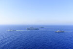 In this photo provided by the Greek National Defence, a French Tonnerre helicopter carrier, center, and French Lafayette frigate, left, are escorted by Greek and French military vessels during a maritime exercise in the Eastern Mediterranean, Thursday, Aug. 13, 2020. Greece's prime minister warmly thanked France Thursday for its decision to boost its military presence in the eastern Mediterranean, where Greek and Turkish warships are closely shadowing each other over a Turkish energy exploration bid in waters Athens claims as its own. (Greek National Defence via AP)
