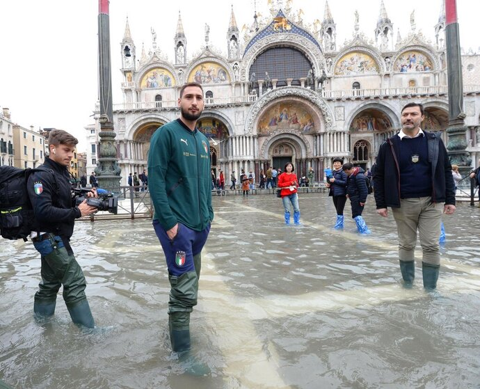 Italy's goalkeeper Gianluigi Donnarumma is seen in St. Mark's Square during a solidarity visit to Venice following the exceptional high water that brought the city to its knees, in Venice, northern Italy, Saturday, Nov. 16, 2019. Four days ago, the Italian lagoon city experienced its worst flooding in more than 50 years. (Andrea Merola/ANSA via AP)
