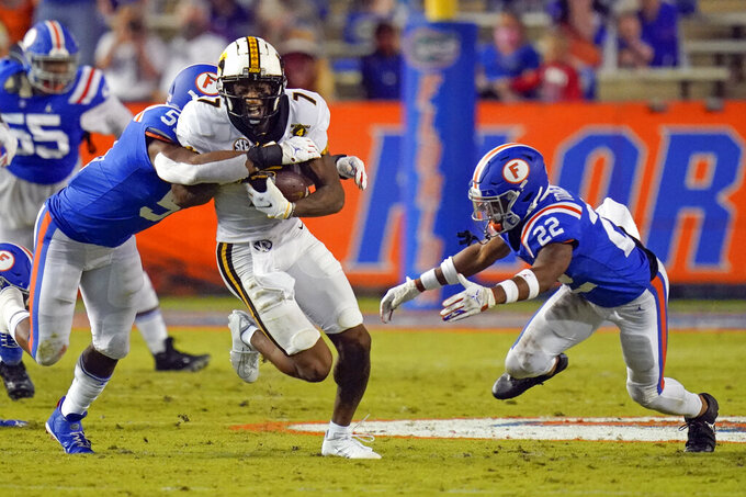 Missouri wide receiver Damon Hazelton (7) runs after a reception, and is tackled by Florida linebacker Ventrell Miller, left, and defensive back Rashad Torrence II (22) during the first half of an NCAA college football game, Saturday, Oct. 31, 2020, in Gainesville, Fla. (AP Photo/John Raoux)