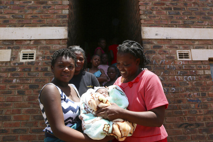 Perseverance Kanyoza, left, shows her newly delivered baby, after the birth in a tiny apartment in the poor suburb of Mbare in Harare, Zimbabwe, Saturday, Nov. 16, 2019. Kanyoza delivered a baby girl with the help of 72 year old grandmother Esther Zinyoro Gwena.  Grandmother Esther Zinyoro Gwena claims to be guided by the holy spirit and has become a local hero, as the country's economic crisis forces closure of medical facilities, and mothers-to-be seek out untrained birth attendants. (AP Photo/Tsvangirayi Mukwazhi)