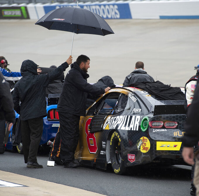 The team of Daniel Hemric covers his car after a NASCAR Cup Series auto race was postponed due to inclement weather conditions Sunday, May 5, 2019, at Dover International Speedway in Dover, Del. (AP Photo/Jason Minto)