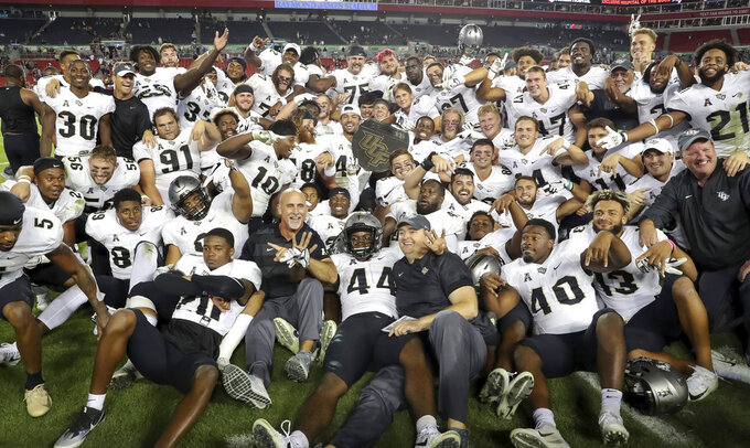 Central Florida celebrates with the War on I-4 trophy after defeating South Florida in an NCAA college football game Friday, Nov. 23, 2018, in Tampa, Fla. (AP Photo/Mike Carlson)