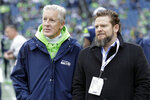 FILE - In this Dec. 30, 2018, file photo, Seattle Seahawks coach Pete Carroll, left, talks with general manager John Schneider before  the team's NFL football game against the Arizona Cardinals in Seattle. There is a clear and obvious need for the Seahawks to address along the defensive line and it happens to be one of the deeper positions of talent in the entire draft. That may be far too simplistic and straightforward for Schneider and Carroll. Schneider is always good for a few surprises in the draft, and more than a couple of trades.   So, while it seems addressing the pass rush — especially with the continuing unknowns around Jadeveon Clowney — is the obvious direction for Schneider and the Seahawks, it's never that clear with Seattle. (AP Photo/Ted S. Warren, File)