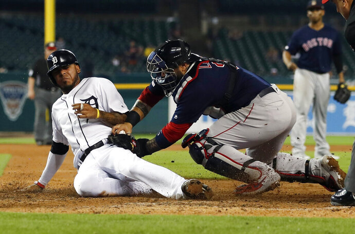 Detroit Tigers' Harold Castro, left, safely beats the tag of Boston Red Sox catcher Sandy Leon to score during the sixth inning of a baseball game, Friday, July 5, 2019, in Detroit. (AP Photo/Carlos Osorio)