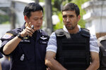 FILE - In this Feb. 20, 2012, file photo, an Iranian bomb suspect Mohammad Kharzei, right, listens to a Thai police officer as he is taken to verify the house where he and other Iranian compatriots rented in Bangkok, Thailand. Thai officials say they have approved the transfer back to Tehran of three Iranians who were involved in a botched 2012 bomb plot. (AP Photo/Sakchai Lalit, File)