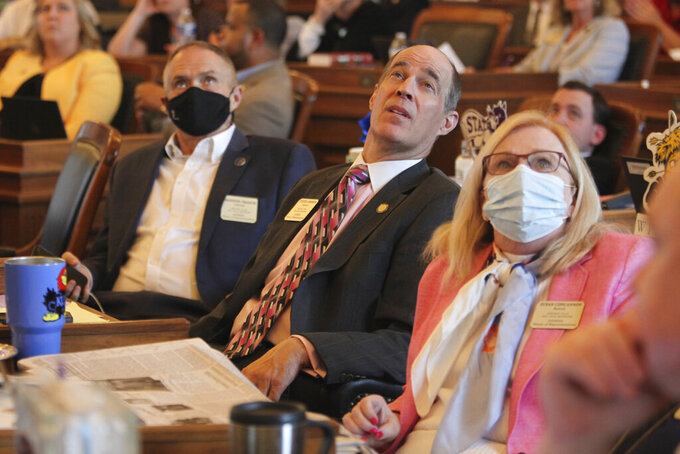 Kansas state Rep. Steven Johnson, center, R-Assaria, watches an electronic tally board in the House as it approves budget legislation, Friday, May 7, 2021, at the Statehouse in Topeka, Kan. To his right is Rep. Shannon Francis, R-Liberal, and to his left, Rep. Susan Concannon, R-Beloit, both members of the House Appropriations Committee, along with Johnson. (AP Photo/John Hanna)