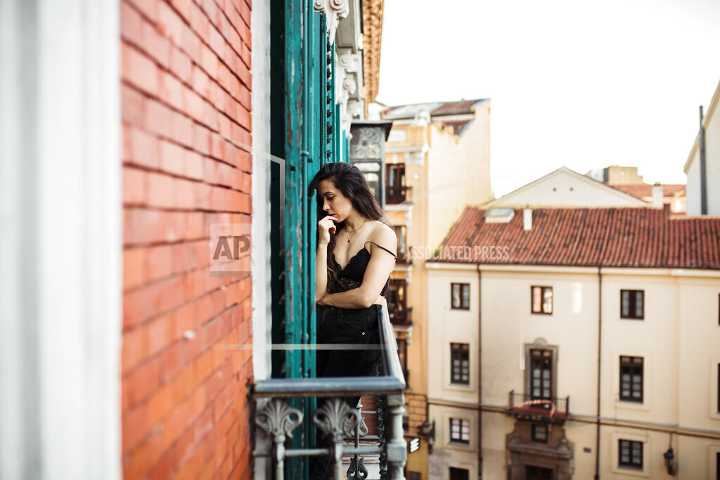 Sad woman with hand on chin standing at balcony