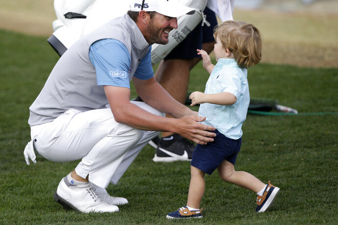 Andrew Landry, left, greets his son, Brooks Landry, on the 18th hole after winning The American Express golf tournament on the Stadium Course at PGA West in La Quinta, Calif., Sunday, Jan. 19, 2020. (AP Photo/Alex Gallardo)