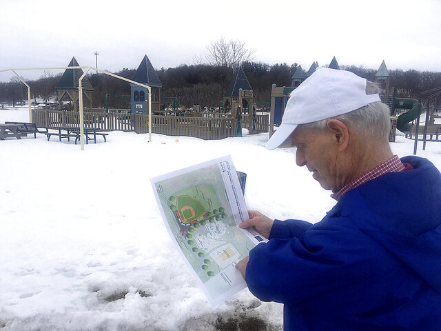 In this Wednesday, Feb. 26, 2020 photo, Bill Schultz looks over a map and rendering of the proposed Miracle Field at Bakken Park in Cottage Grove, Wis.  Schultz wasn't allowed to play Little League baseball in the 1950s because of his wooden prosthetic leg. (Barry Adams/Wisconsin State Journal via AP)