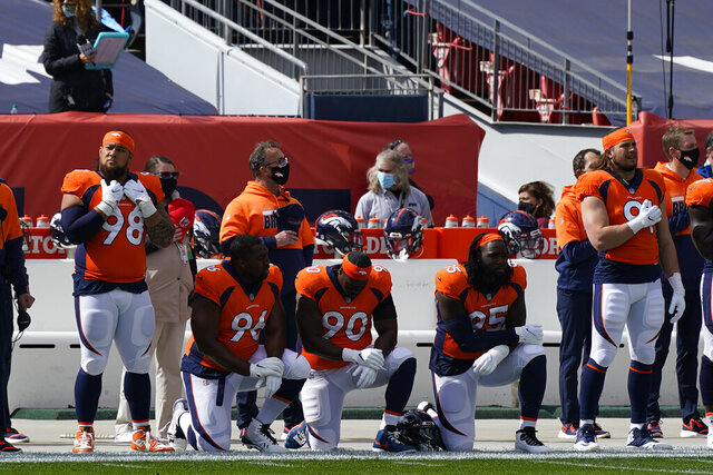 Denver Broncos defensive end Shelby Harris (96) kneels alongside defensive end DeShawn Williams (90) and running back Melvin Gordon during the playing of the national anthem before an NFL football game against the Tampa Bay Buccaneers, Sunday, Sept. 27, 2020, in Denver. (AP Photo/David Zalubowski)