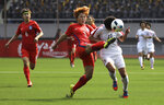 FILE - In this April 7, 2017, file photo, South Korea's Shin Damyeong, left, and North Korea's Ri Kyong Hyang, right, go after the ball during their AFC Women's Asian Cup Jordan 2018 qualifying soccer match at the Kim Il Sung Stadium in Pyongyang, North Korea. The South Korean men's national soccer team's path to the 2022 World Cup in Qatar will include a crucial road match against North Korea, but it's unclear whether a rare match between the Koreas in Pyongyang will materialize considering the political tension between the rivals. (AP Photo/Jon Chol Jin, File)