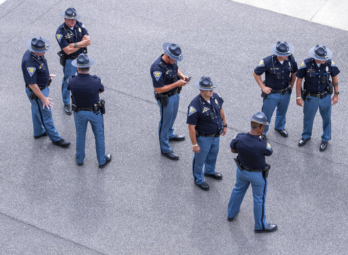 A group of Indiana State Police troopers stage in the pit area during a NASCAR Cup Series auto race at Indianapolis Motor Speedway, Sunday, Aug. 15, 2021, in Indianapolis. (AP Photo/Doug McSchooler)