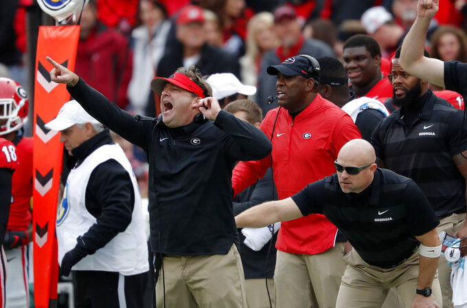 Georgia head coach Kirby Smart, left, is restrained by an assistant coach as he yells to his players from the sideline during the second half an NCAA college football game against Georgia Tech, Saturday, Nov. 24, 2018, in Athens, Ga. Georgia won 45-21. (AP Photo/John Bazemore)