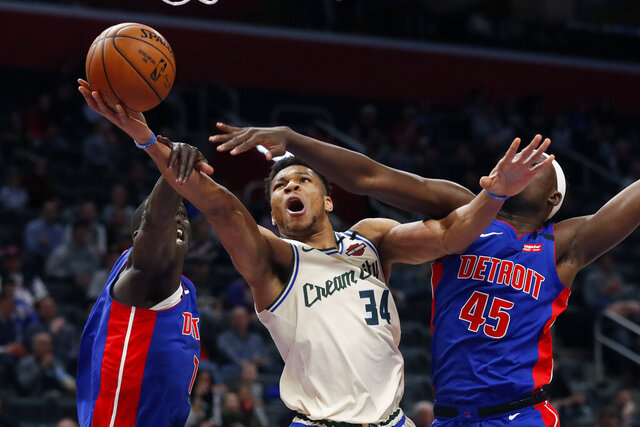Milwaukee Bucks forward Giannis Antetokounmpo (34) makes a layup as Detroit Pistons forwards Thon Maker, left, and Sekou Doumbouya (45) defend during the first half of an NBA basketball game, Thursday, Feb. 20, 2020, in Detroit. (AP Photo/Carlos Osorio)