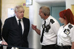 Britain's Prime Minister Boris Johnson talks with prison staff during a visit to Leeds prison, Northern England, Tuesday Aug. 13, 2019.  In an announcement on Sunday Johnson promised more prisons and stronger police powers in an effort to fight violent crime. ( AP Photo/Jon Super)