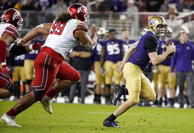 Washington quarterback Jake Browning, right, runs away from Utah defensive tackle Leki Fotu (99) during the first half of the Pac-12 Conference championship NCAA college football game in Santa Clara, Calif., Friday, Nov. 30, 2018. (AP Photo/Tony Avelar)
