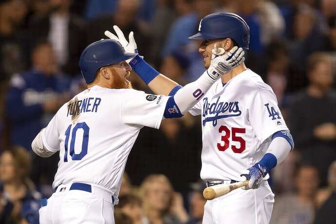 Los Angeles Dodgers' Justin Turner, left, and Cody Bellinger celebrate Turner's solo home run during the third inning of the team's baseball game against the Chicago Cubs in Los Angeles, Friday, June 14, 2019. (AP Photo/Kyusung Gong)