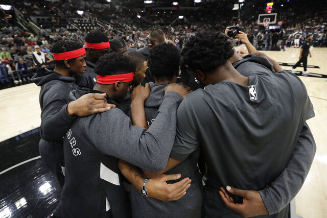 Toronto Raptors players huddle together following a moment of silence for Kobe Bryant before an NBA basketball game against the San Antonio Spurs in San Antonio, Sunday, Jan. 26, 2020. (AP Photo/Eric Gay)