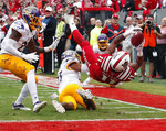 North Carolina State's Jakobi Meyers (11) gets flipped over backwards as he scores a touchdown against East Carolina's Daniel Charles (27) and Warren Saba (17) during the first half of NCAA college football game in Raleigh, N.C., Saturday, Dec. 1, 2018. (AP Photo/Chris Seward)